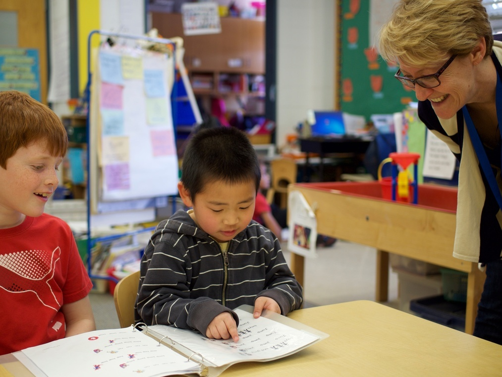 Slideshow: Kindergarten student reads to his second grade buddy as teacher looks on