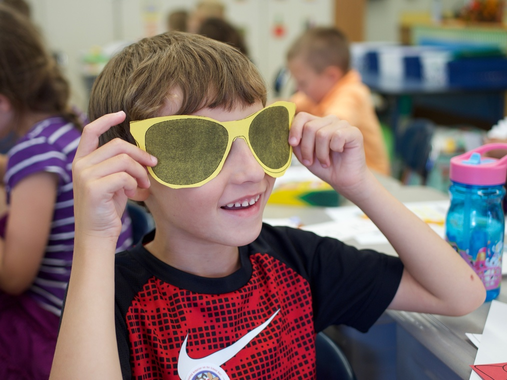 Slideshow: Boy with yellow paper sunglasses.
